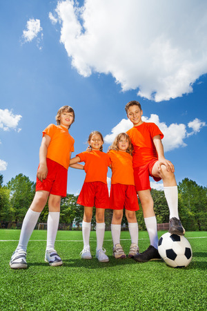 hugging knees: Happy kids of different height with football Stock Photo
