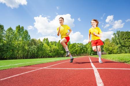 pista de atletismo: Dos chicos corriendo juntos en la competencia Foto de archivo
