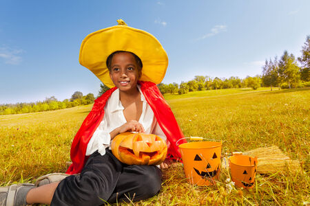 Halloween boy sits on yellow grass with pumpkin photo
