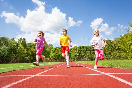 running on track: Smiling children running marathon together
