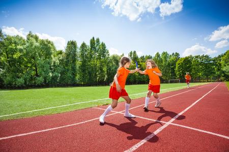 carrera de relevos: Chica con carreras bastón y se lo pasa a otro corredor