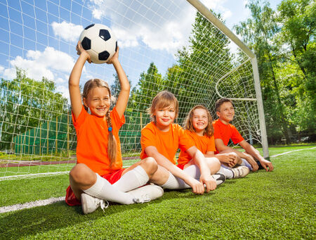 children hands: Children sit together on field with football