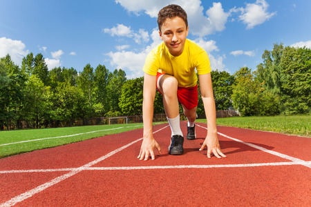 legs apart: Boy in position to run with arms on the ground Stock Photo