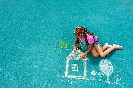 dětské hřiště: Malá černá holčička kreslení křídou sněmovna obrázku Reklamní fotografie