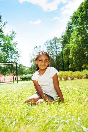 fille noire: Portrait de jeune fille noire dans le parc assis sur la pelouse