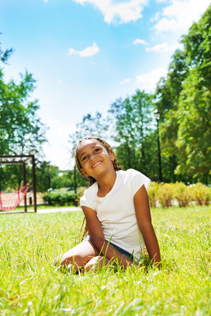 Portrait of black girl in park dreaming on lawn photo