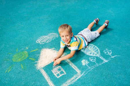 Little boy drawing chalk image on the ground photo