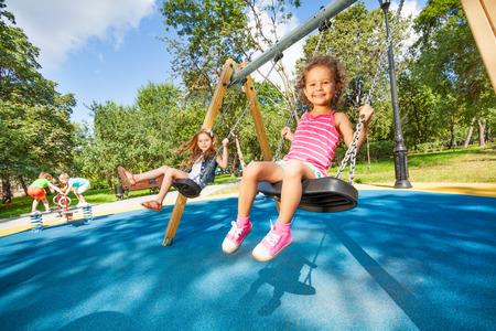 enfant qui joue: Les enfants se balancer sur aire de jeux Banque d'images