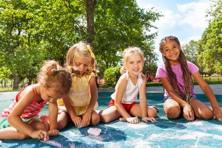 Girls draw image with chalk on playground photo