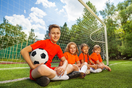 Kids sit in row near woodwork with football photo