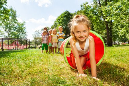 children at play: Nice girl crawling thought the tube in park
