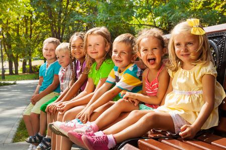 Děti na lavičce v parku v létě