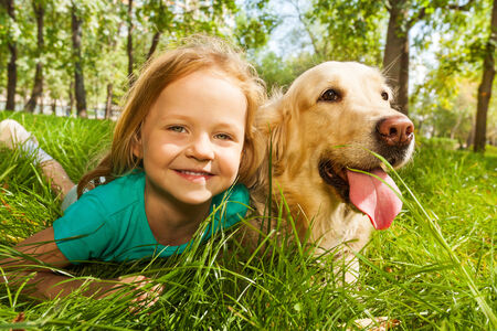 Little blond girl with her retriever dog photo