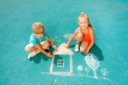 Boy and girl draw chalk image sitting toggether photo