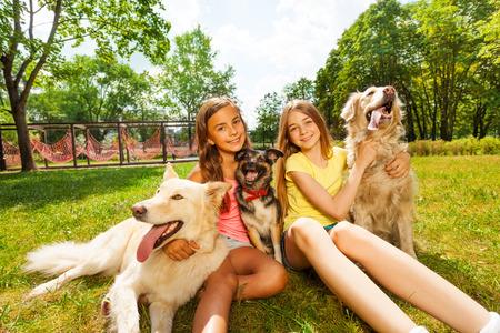 chien: Deux heureux adolescentes assises dans le parc avec leurs chiens sur la journée ensoleillée d'été