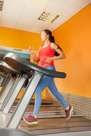 Attractive Asian girl running on the treadmill