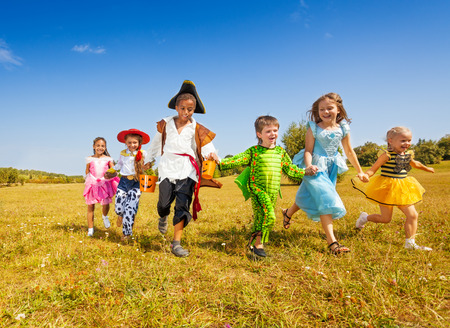 Large group of kids in Halloween costumes run