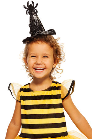 Girl in striped bee costume wearing spider hat photo