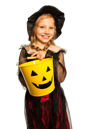 In witch costume holding Halloween bucket photo