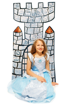 Girl in princess dress sit near cardboard castle photo