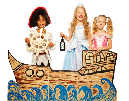 theatre costumes: Three kids, pirate and princess on cardboard ship Stock Photo