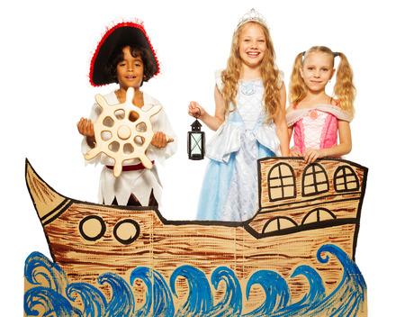 Tres niños, pirata y la princesa en el barco de cartón Foto de archivo - 31454995
