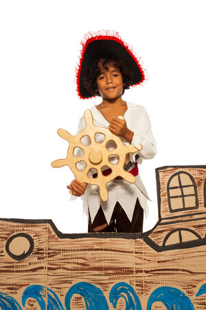 Little boy playing being pirate on cardboard ship photo