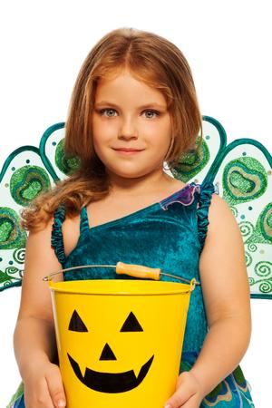 Little girl with Halloween candy bucket, costume photo