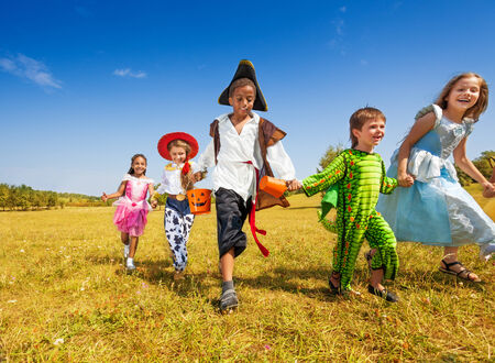 Group of kids with costumes running in park photo