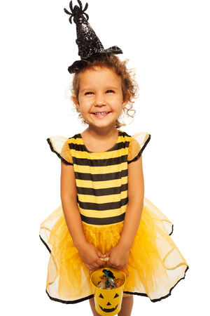 carved pumpkin: Little bee costume with candy Halloween bucket  Stock Photo