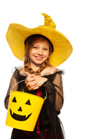 Girl in witch costume and spooky Halloween bucket Banque d'images