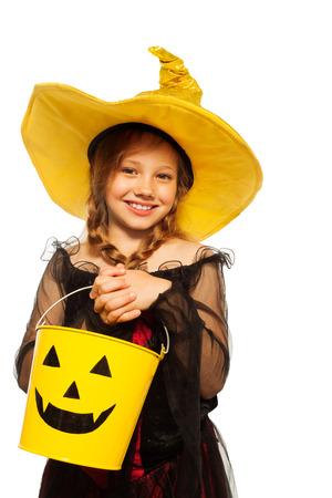 Chica en traje de bruja y espeluznante cubo de Halloween