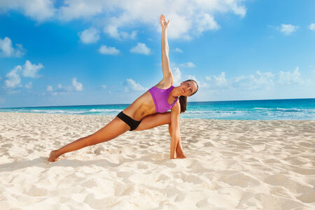 legs apart: Woman on beach with arm up and legs apart