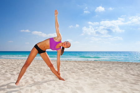 Smiling young woman stretching body with  arm up photo