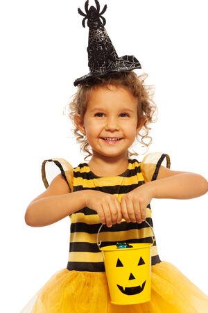 Little girl in bee costume with Halloween bucket photo