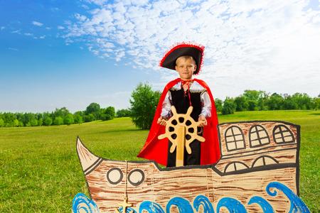 Boy als Pirat steht auf Schiff und hält das Ruder Standard-Bild - 31912938