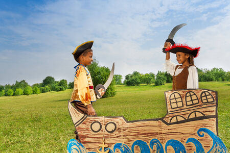 dueling: Two African kids as pirates dueling with swords Stock Photo