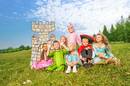 Children in festival costumes sit on grass photo
