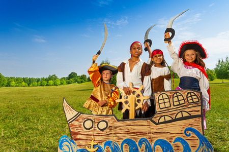 Four kids in pirate costumes behind ship Фото со стока - 31913878