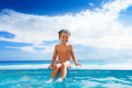 Bambino seduto sul confine lapidato con le gambe in acqua