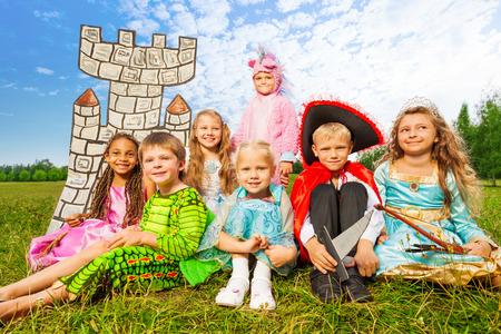 Smiling children in festival costumes sit close Foto de archivo
