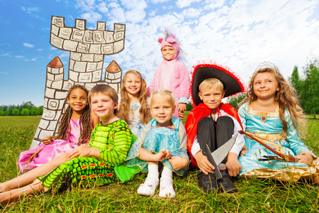 Smiling children in festival costumes sit close Stock Photo