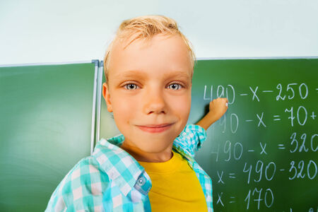 Boy close up view who stands near blackboard photo