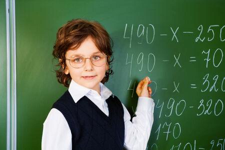 Clever boy holds chalk near blackboard photo