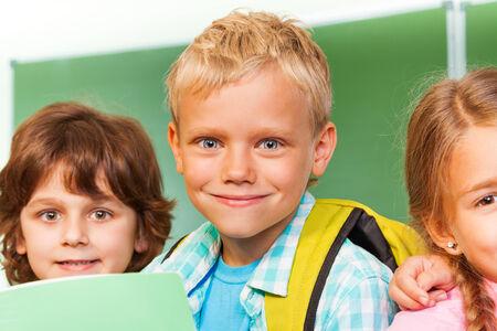 school friends: Children near each other in front of blackboard