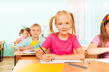 niños escribiendo: Niños sentados a la mesa en el aula y la escritura Foto de archivo