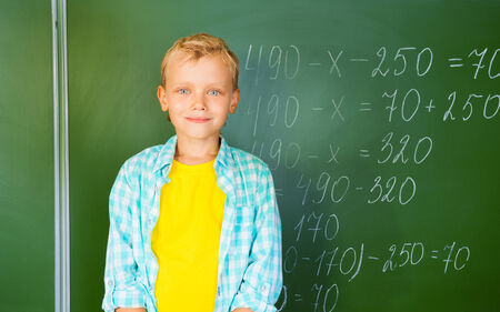 Boy in bright T-shirt stands near blackboard photo