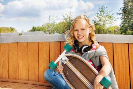 Blond smiling girl with headphones and  skateboard photo