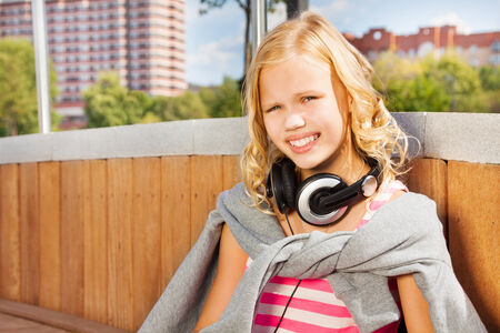 Close view of girl wearing headphones, sweatshirt photo