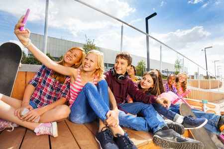 multinational: Blond girl making selfie of her and friends